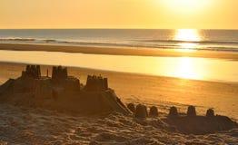 Grande castello della sabbia sulla spiaggia alla sera Fotografia Stock