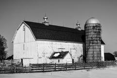 Grande celeiro branco com silo na neve do inverno foto de stock