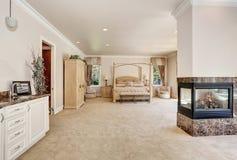 Grande chambre à coucher crémeuse principale de tons dans la maison de luxe Image stock