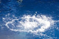 Grande éclaboussure dans l'eau bleu-foncé Photo libre de droits