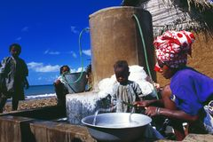 Grande Comores: A comorian woman washing cloth, her children obeying her royalty free stock photo