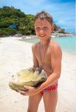 Grande conchiglia tenuta da un giovane ragazzo Fotografia Stock Libera da Diritti