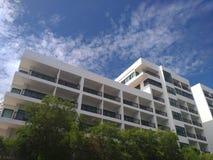 A grande construção com a nuvem e a árvore do céu azul fotos de stock