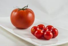 Grande contra o tomate pequeno, um tamanho importa conceito pequeno Fotografia de Stock