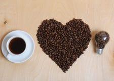 Grande coração feito de feijões, de xícara de café e de bulbo de café com feijões de café para dentro em um fundo de madeira clar Fotografia de Stock