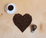 Grande coração feito de feijões, de xícara de café e de bulbo de café com feijões de café para dentro em um fundo de madeira clar Foto de Stock Royalty Free