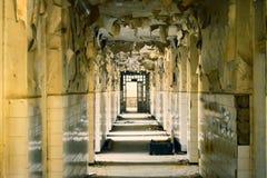 Grande corridoio abbandonato con le grandi finestre rotte e esfoliare le pareti nell'asilo fotografie stock