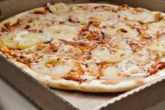 Grande coupe de pizza en morceaux dans une boîte en carton photo libre de droits