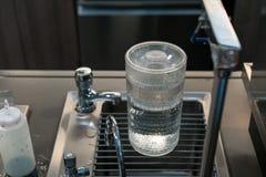Grande cruche d'eau complètement d'eau douce pure sur l'évier moderne photos libres de droits