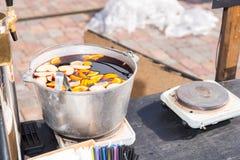Grande cubeta metálica com vinho ferventado com especiarias no fogão velho exterior Imagem de Stock Royalty Free