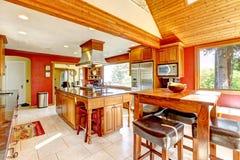 Grande cucina con le pareti rosse ed il soffitto di legno. Fotografia Stock