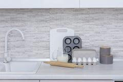Grande cucina leggera Stoviglie per la cottura, la muffa del dolce ed il vassoio con le uova sulla tavola Fotografie Stock
