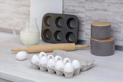 Grande cucina leggera Stoviglie per la cottura, la muffa del dolce ed il vassoio con le uova sulla tavola Fotografia Stock