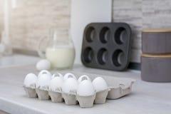 Grande cucina leggera Stoviglie per la cottura, la muffa del dolce ed il vassoio con le uova sulla tavola Immagine Stock