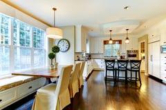 Grande cucina moderna di lusso bianca e tabella pranzante Fotografia Stock Libera da Diritti