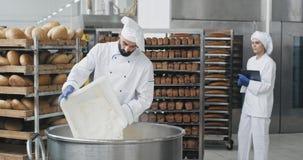 Grande cuoco unico dell'industria della panificazione in un'uniforme speciale che prepara la pasta per aggiungere una certa farin video d archivio