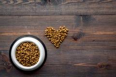 Grande cuvette d'animal familier - aliments pour chats se renversant dans la forme de coeur sur la maquette en bois de vue supéri Photo stock