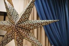 Grande decorazione della stella del cartone per il Natale nella sala Fotografia Stock Libera da Diritti