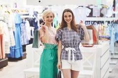 Grande dia para comprar Duas mulheres bonitas com os sacos de compras que olham se com sorriso ao andar no fotografia de stock