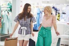 Grande dia para comprar Duas mulheres bonitas com os sacos de compras que olham se com sorriso ao andar no foto de stock royalty free