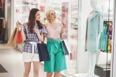 Grande dia para comprar Duas mulheres bonitas com os sacos de compras que olham se com sorriso ao andar no imagens de stock royalty free