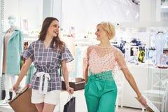 Grande dia para comprar Duas mulheres bonitas com os sacos de compras que olham se com sorriso ao andar no fotos de stock royalty free