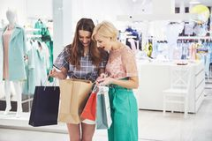 Grande dia para comprar Duas mulheres bonitas com os sacos de compras que olham se com sorriso ao andar no foto de stock