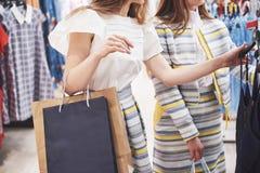 Grande dia para comprar Duas mulheres bonitas com os sacos de compras que olham se com sorriso ao andar no imagens de stock