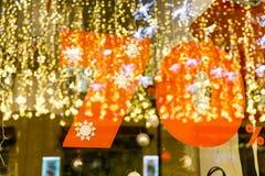 Grande disconto da venda 70%, uma bandeira no vidro com a reflexão de festões do ` s do ano novo Fotos de Stock Royalty Free