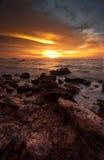 Grande e bella vista del tramonto alla spiaggia con la pietra sulla priorità alta Immagine Stock
