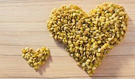 Grande e piccolo cuore dalla lenticchia su fondo di legno, alimento salutare Fotografia Stock