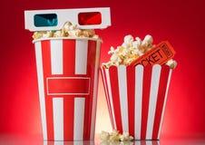 Grande e scatola di popcorn media con 3D i vetri, biglietti di film su un rosso Immagini Stock Libere da Diritti