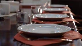 Grande e tabela lustrada chique, em que há placas e vidros Ajuste da tabela em um restaurante aristocrático video estoque