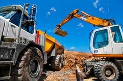 Grande, escavatore industriale sul sito della nuova costruzione Immagine Stock