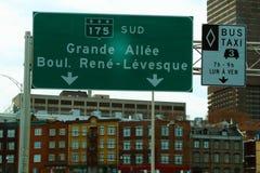 A grande estrada assina dentro as construções do fundo em Montreal foto de stock