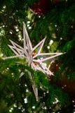 A grande estrela decora na árvore e nas luzes de Natal verde borradas no fundo Decorationsn do feriado fotografia de stock