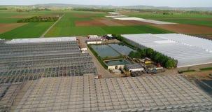 Grande estufa moderna, um grande complexo agrícola, voando sobre uma estufa cercada por campos verdes video estoque