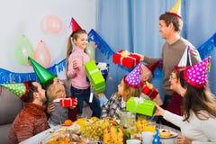 Grande família que apresenta presentes à menina durante a festa de anos imagens de stock