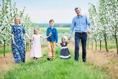 Grande famiglia all'aperto Tre bambini e genitori nel giardino di fioritura di primavera fotografie stock libere da diritti