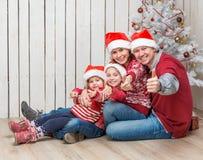 Grande famiglia in cappelli di Santa vicino all'albero di Natale fotografia stock