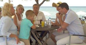 Grande famiglia che si siede alla tavola sulla costa di mare in città di Perea, Grecia archivi video