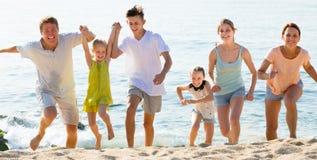 Grande famiglia di risata sulla spiaggia il giorno soleggiato Fotografia Stock