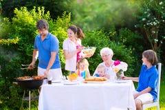 Grande famiglia felice che gode della griglia del bbq nel giardino Fotografie Stock Libere da Diritti