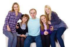 Grande famiglia sullo strato - quattro donne ed un uomo Immagine Stock