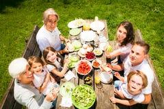 Grande famille ayant un pique-nique dans le jardin Image stock