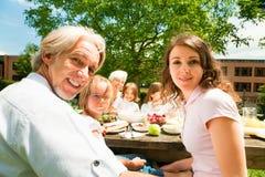 Grande famille ayant un pique-nique dans le jardin Image libre de droits
