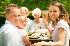 Grande famille ayant un pique-nique dans le jardin Photo stock