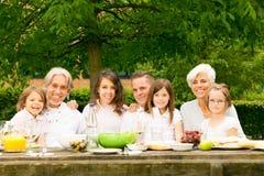 Grande famille ayant un pique-nique dans le jardin Photos stock