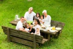 Grande famille ayant un pique-nique dans le jardin Photo libre de droits