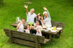 Grande famille ayant un pique-nique dans le jardin Photographie stock libre de droits